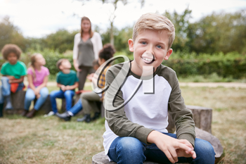 Portrait Of Boy On Outdoor Activity Camping Trip Sitting Around Camp Fire With Friends