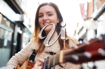 Portrait Of Young Female Musician Busking Playing Acoustic Guitar And Singing Outdoors In Street