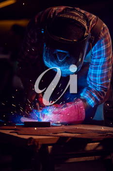 Male Blacksmith Wearing Protective Safety Visor Arc Welding Metalwork In Forge