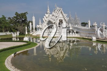White fabulous palace in Southeast Asia. The elegant facade is reflected in a pond with live fish