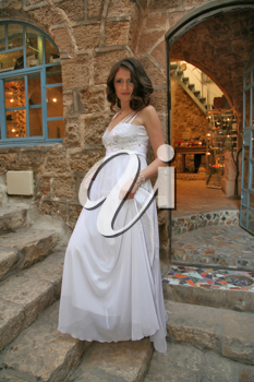 The beautiful bride in a white dress on a background of an ancient workshop of the artist
