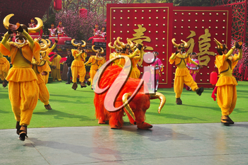 Performance of dancing ensemble in picturesque suits on celebrating of the Chinese New year
