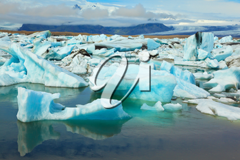 The blue and emerald icebergs and ice floes floating in the gulf Jökulsárlóн in Iceland. Sunrise.