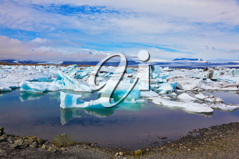 Reflection. Blue and turquoise icebergs and ice floes are reflected in smooth water of the Gulf Jökulsárlón in Iceland.  Sunrise