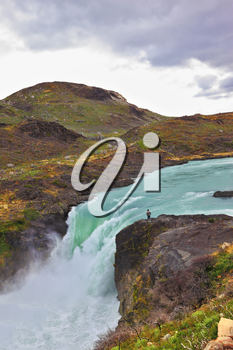 Gorgeous National Park in Chilean Patagonia. Affluent bustling Salto Grande waterfall with emerald water. On the edge of the cliff stands tourist