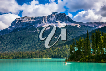 Emerald Lake in the Rocky Mountains of Canada. The green lake surrounded by a coniferous forest. Group of tourists crosses the lake in a rowboat