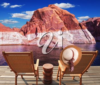 Walk to the tourist boat on Lake Powell on the Colorado River. At the stern of the vessel are two deck chairs. On the back of one hanging elegant ladies straw hat.