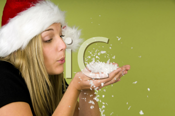 Royalty Free Photo of a Woman in a Santa Hat Blowing Snow