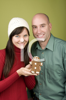 Royalty Free Photo of a Couple Holding a Gingerbread Man
