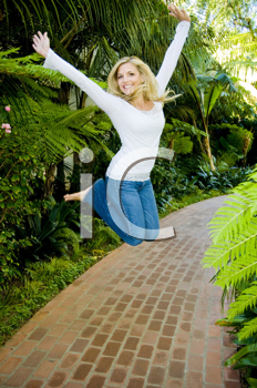 Royalty Free Photo of a Woman Jumping on a Garden Path