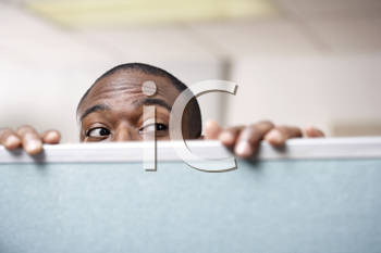 Royalty Free Photo of a Businessman Looking Over a Cubicle
