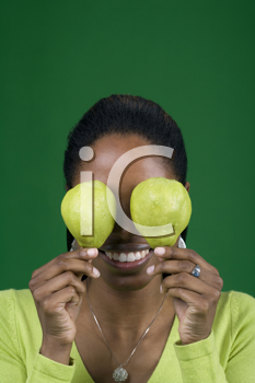 Royalty Free Photo of a Black Woman Holding Pears Over Her Eyes