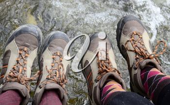 Legs of hikers with same boots  hanging
