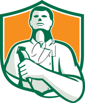 Illustration of a barber holding a hair clipper facing front looking up set inside shield crest done in retro style on isolated background.