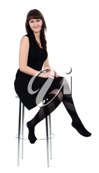 Girl in black dress sitting barefoot on a high chair, isolated on a white background.