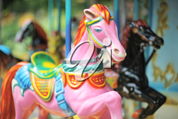 Pink and black horses on the carousel in City Park