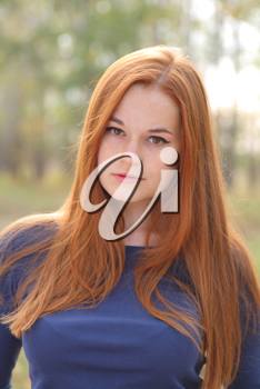 Natural beautiful red-haired girl head and shoulders shot outdoor