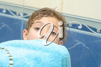 boy with a blanket (blue towel) in hands before head