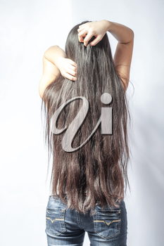 Girl with long fair hair from back, on white background.