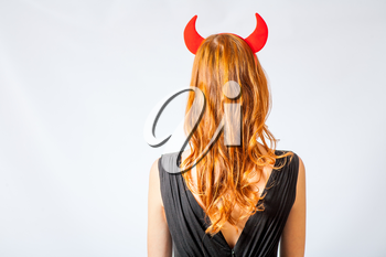 redhead girl with red  horns looks like pretty Devil