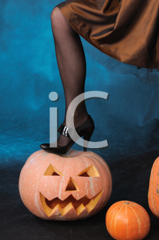 Royalty Free Photo of a Woman Standing on a Pumpkin