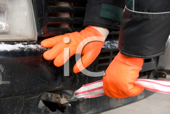 Royalty Free Photo of a Man Putting Towing Cables on a Car
