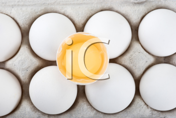 Royalty Free Photo of a Carton of Eggs With a Broken One