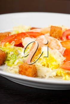 Salad of tiger shrimps, lettuce, chinese cabbage, tomato, garlic rusk, parmesan cheese and sauce
