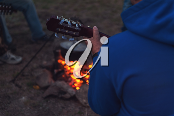 Closeup photo of the man playing o guitar near the campfire