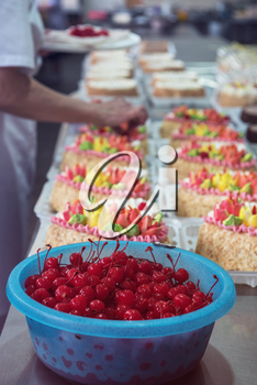 Bowl of cherry on cake production in factory