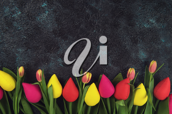 Handmade and real tulips on darken concrete background for Mother's Day, spring time or Easter theme.