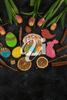Tulips and gingerbread cookies on darken concrete background for Easter.