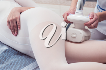 Woman in special white suit getting anti cellulite massage in a spa salon. LPG, and body contouring treatment in clinic. Lipomassage procedure on female body.