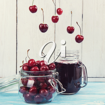 Cherry juice with glass jar of berries on blue wooden background