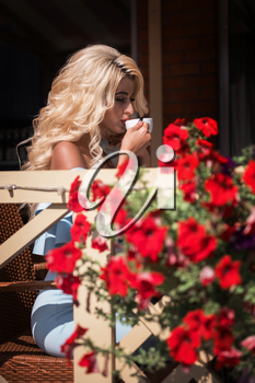 Beauty sensual woman in elegant blue dress in cafe. Young woman sitting in cafe with cup of coffee in summer day.