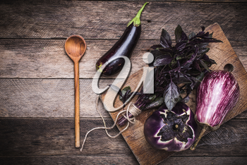 Aubergines, basil and spoon on wooden table. Rustic style and autumn food photo