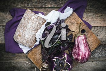 Aubergines basil and bread on chopping board and wood. Rustic style and autumn food photo