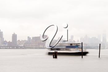 New York, USA-June 2, 2015: East River Ferry coming in for docking on a foggy day.