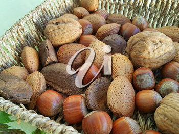 Mix of different types nuts close-up in wicker dish