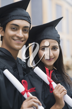 Couple in graduation gowns holding diplomas and smiling