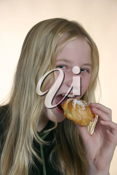 Royalty Free Photo of a Girl Eating a Pastry