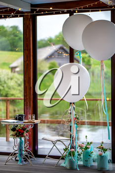Luxury decorated place for wedding reception in restaurant. Wedding place in restaurant decorated with balloons, ribbons and flowers.