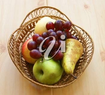 Basket with fresh fruit on wooden table
