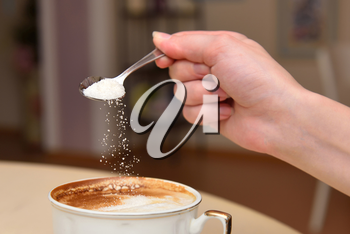 The girl's hand pours sugar into her coffee.