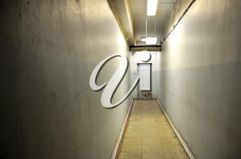 Royalty Free Photo of a Long, Dark Corridor With a Door at the End