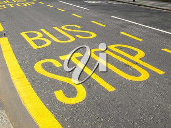 Yellow painted bus stop sign on a street - Selective colour over desaturated background