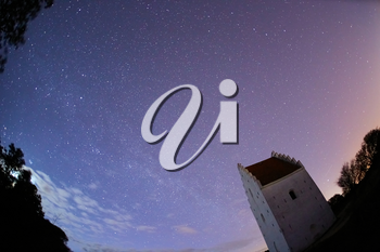 a beautiful shot of a small church tower in the night sky