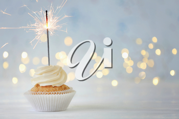 Delicious cupcake with sparkler on white table against blurred lights