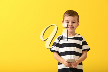 Cute little boy with smartphone on color background