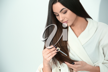Beautiful young woman applying serum onto her healthy long hair at home�